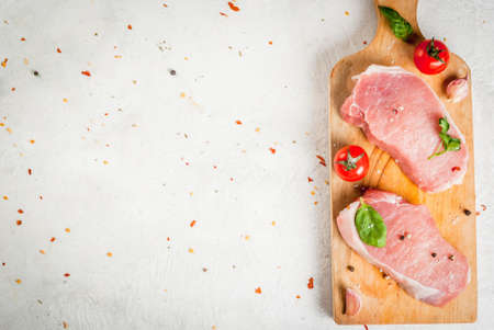 unprepared: Raw pork, steak, cutlet. Meat, a source of protein. On a cutting board, on a white stone table. With spices, herbs and tomatoes for cooking. Copy space top view