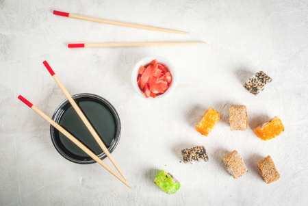 Concept of Japanese food: sticks and sushi, soy sauce and pickled ginger on a white stone table. Top view copy space Stock Photo