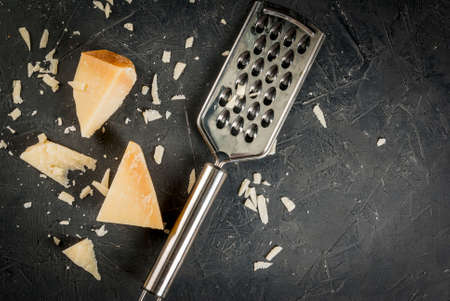 Ingredients of Italian cuisine.Parmesan grated and a piece, with a grater on a dark concrete table. Top view copy space