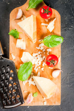 Ingredients of Italian cuisine.Parmesan grated and a piece, with a grater, basil leaves, garlic and cherry tomatoes on cutting board on dark concrete table. Top view copy space