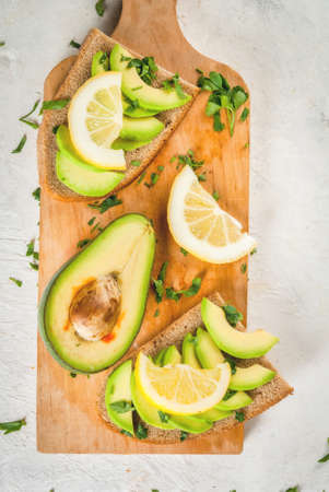 Healthy diet food. Spring meal. Sandwiches of black bread with avocado, lemon and greens. With ingredients on cutting board on white stone table, top view copy space