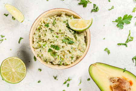 Homemade guacamole in bowl, served with lime lemon and parsley, with half of avocado on white concrete table. Top view Stock Photo - 76338185