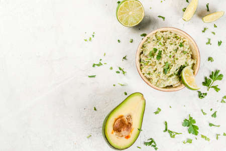 Homemade guacamole in bowl, served with lime lemon and parsley, with half of avocado on white concrete table. Top view copy space Stock Photo - 76338191