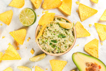 Homemade guacamole in bowl, served with tortilla nachos lime lemon and parsley, with half of avocado on white concrete table. Top view Stock Photo - 76338192