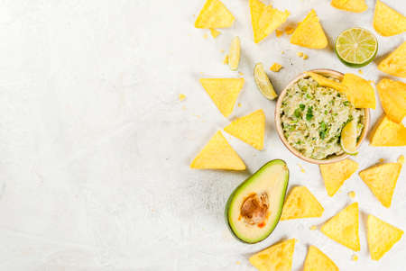 Homemade guacamole in bowl, served with tortilla nachos lime lemon and parsley, with half of avocado on white concrete table. Top view copy space
