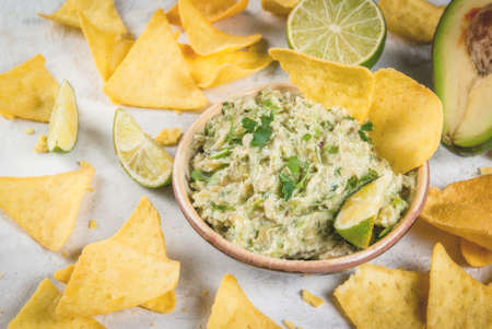 Homemade guacamole in bowl, served with tortilla nachos lime lemon and parsley, with half of avocado on white concrete table. Stock Photo - 76338196