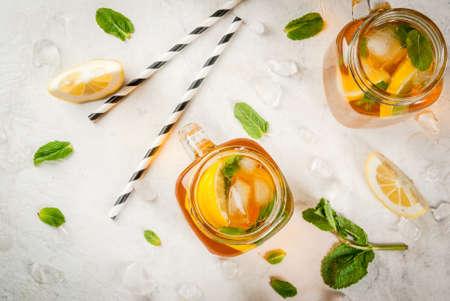 氷、ミントとレモンで冷蔵の夏茶。白い石のテーブルにメーソン ジャーの 2 つの部分。コピー スペース平面図