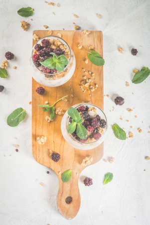 Dietary vegan healthy breakfast. Yogurt and granola with fresh blackberry oranges and mint in a glass. On a white table, on a cutting board. Copy space top view