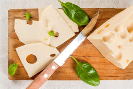 Maasdam radomer cheese on a cutting board, with leaves of basil. On a white stone concrete table. Copy space top view