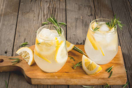 Summer refreshments. Detox water. Lemonade. Tonic with ice, lemon and rosemary, on an old wooden rustic table. Copy space Stock Photo