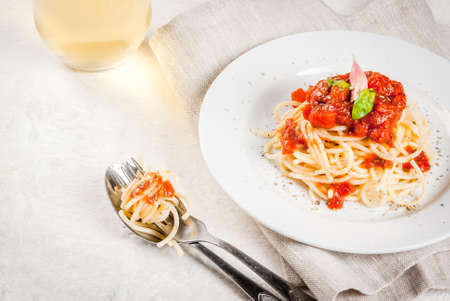 Italian cuisine. Lunch or dinner. A serving of spaghetti pasta with tomato marinara sauce and basil on a white concrete table. With a glass of white wine. Copy space
