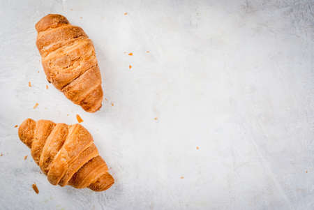 Two fresh homemade croissants on a white concrete table. Top view copy space Stock Photo