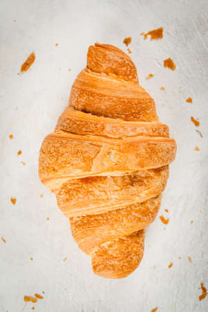 Fresh homemade croissant on a white concrete table. Top view copy space Stock Photo