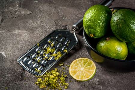 Fresh organic tropical citrus fruits lime in a black bowl on a gray concrete background. Whole and half. With a grater and grated rind. Copy space top view