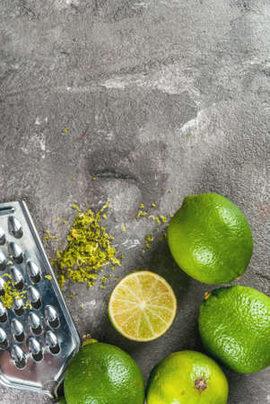 Fresh organic tropical citrus fruits lime in a black bowl on a gray concrete background. Whole and half. With a grater and grated rind. Copy space top view vertical Stock Photo