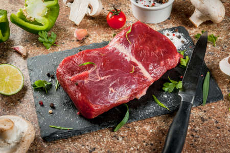 Fresh raw beef meat on slate cutting board on stone table. With fresh vegetables (tomato, bell pepper, mushrooms), spices (salt, pepper), garlic and herbs - parsley and tarragon. Copy space top view Stock Photo - 76918568