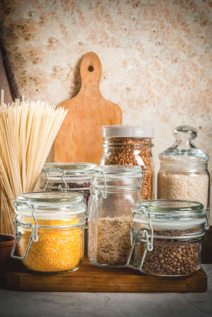 Selection of gluten-free products, cereals: xanthan gum. buckwheat,Rice, rice noodles, chickpeas, lentils, corn, beans, oatmeal. In the home kitchen, in jars. Copy space vertical