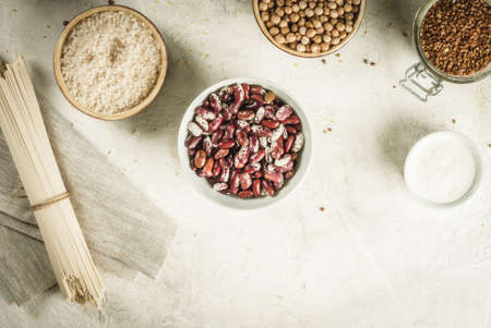 Selection of gluten-free products, cereals: xanthan gum. buckwheat,Rice, rice noodles, chickpeas, lentils, corn, beans, oatmeal. In bowls and jars, the top view on white table top view copy space Stock Photo - 76960537