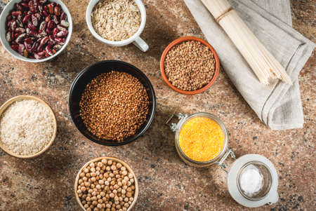 Selection of gluten-free products, cereals: xanthan gum. buckwheat,Rice, rice noodles, chickpeas, lentils, corn, beans, oatmeal. In bowls and jars, the top view on stone table top view copy space Stok Fotoğraf