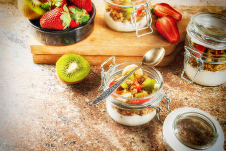 Healthy breakfast. Diet. Overnight oatmeal in a can, muesli. Yogurt with homemade granola and organic fruits - kiwi, banana, strawberry. On the stone table. With ingredients and spoons. Copy space