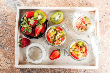 Healthy breakfast. Diet. Overnight oatmeal in a can, muesli. Yogurt with homemade granola and organic fruits - kiwi, banana, strawberry. On tray on stone table. top view Stock Photo