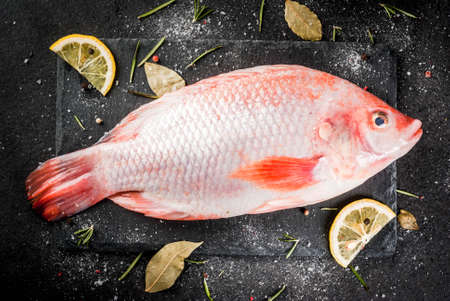 Raw fish red tilapia on a chopping board on a black stone table, with spices, lemon and herbs for cooking. Top view
