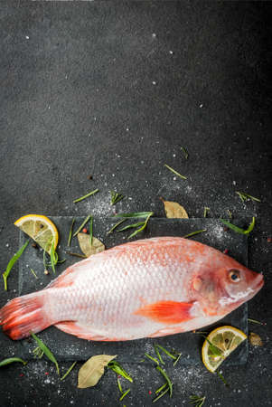 Raw fish red tilapia on a chopping board on a black stone table, with spices, lemon and herbs for cooking. Top view copy space Imagens