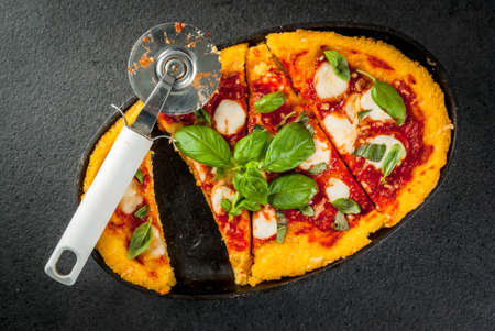 Italian Cuisine. Gluten-free food. Traditional national dish Pizza di polenta - pizza, cooked on corn polenta. On a black stone table, in a portioned skillet for baking. Top view copy space Stock Photo