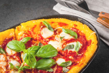 pizza base: Italian Cuisine. Gluten-free food. Traditional national dish Pizza di polenta - pizza, cooked on corn polenta. On a black stone table, in a portioned skillet for baking. Copy space