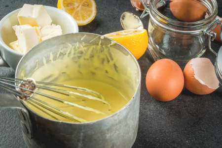 Traditional basic sauces. French cuisine. Hollandaise sauce in a metal saucepan, with ingredients for cooking - eggs, butter, lemons. On a black stone table. Copy space top view Banco de Imagens