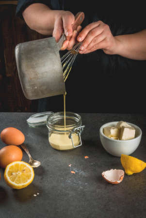 Traditional basic sauces. French cuisine. Person in the frame is preparing Hollandaise sauce. In a metal saucepan, with ingredients - eggs, butter, lemons. On black stone table. Female hands. Stock Photo - 77329251