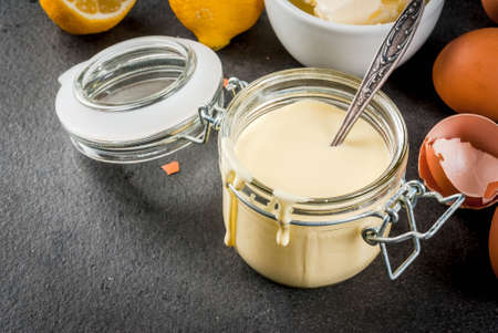 Traditional basic sauces. French cuisine. Hollandaise sauce in glass jar, with ingredients for cooking - eggs, butter, lemons. On a black stone table. Copy space