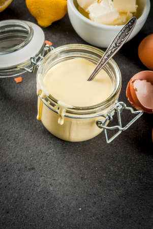 Traditional basic sauces. French cuisine. Hollandaise sauce in glass jar, with ingredients for cooking - eggs, butter, lemons. On a black stone table. Copy space Stock Photo - 77329253