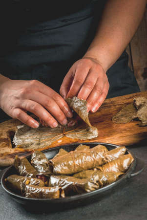 Eastern (Armenian, Turkish) traditional national food. Vegan food. Person in the frame is preparing a dolma - meat with vegetables, wrapped in grape leaves. Homemade food. Female hands.