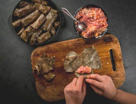Eastern (Armenian, Turkish) traditional national food. Vegan food. Person in the frame is preparing a dolma - meat with vegetables, wrapped in grape leaves. Homemade food. Female hands. Top view Imagens