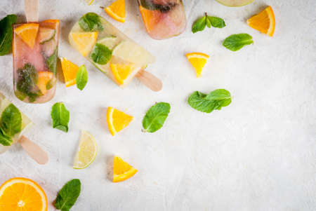 Homemade ice cream. Frozen drinks. Fresh fruits, citrus. Ice cream of red, white sangria, lemonade or mojito. With oranges, lime, mint, apples. White stone table, ingredients. top view
