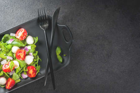 Light spring salad from leafy vegetables, with arugula, basil, mozzarella cheese balls and tomatoes. On a black rectangular plate, with a knife and fork. On a black stone table. Top view copy space