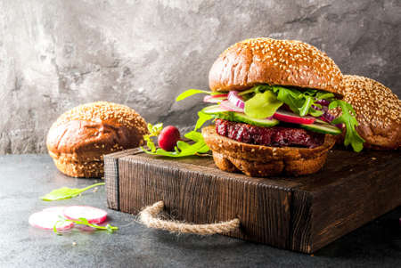Healthy vegan burgers with beets, carrots, spinach, arugula, cucumber, radish and tomato sauce, whole grain buns on a rustic wooden board on a dark stone background, selective focus, copy space Standard-Bild
