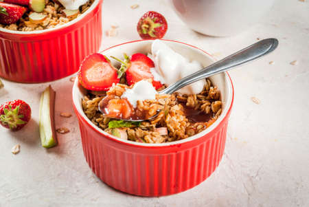Healthy breakfast. Oatmeal granola crumble with rhubarb, fresh strawberries and blackberries, seeds and ice cream in baked bowls, decorated with mint, on white stone concrete table, copy space