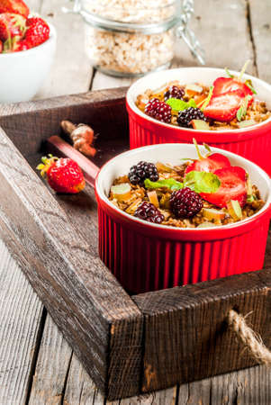 Healthy breakfast. Oatmeal granola crumble with rhubarb, fresh strawberries and blackberries, seeds and ice cream in baked bowls, decorated with mint, on a wooden rustic table in old tray, copy space