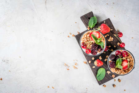 Healthy breakfast. Summer berries and fruits. Homemade Greek yoghurt with granola, blackberries, strawberries, cherries and mint. On white concrete stone table, in glasses. Copy space top view