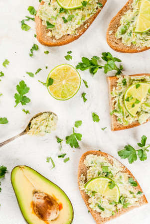 Homemade sandwich toasts with with guacamole, lime lemon and parsley on white table, copy space top view Stock Photo - 78716180