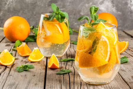 infused: Summer refreshing orange drink. Detox, diet, infused. Variations on lemonade. Mineral water with pieces of fresh orange and mint. On a rustic wooden table with grey wall. Vertical, copy space