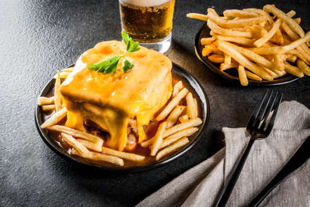 Traditional Portuguese snack food. Francesinha sandwich of bread, cheese, pork, ham, sausages, with tomato beer sauce and French fries. With a glass of beer and potatoes. On black table. Copy space