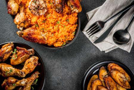 서 아프리카 국가 요리. Jollof 밥에 구운 닭 날개와 튀긴 바나나 플랜 튼. 회색 석 테이블. 공간 위쪽보기 복사