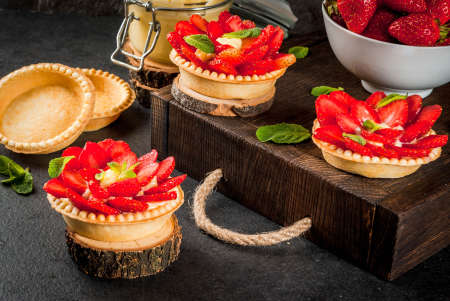 Summer and spring dessert. Home pies tartlets with custard and strawberries, decorated with mint and powdered sugar. On black stone table, rustic, with wooden board, tray. Copy space