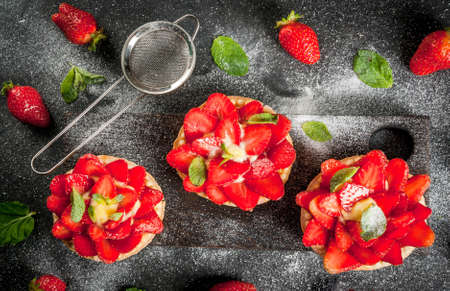 Summer and spring dessert. Home pies tartlets with custard and strawberries, decorated with mint and powdered sugar. On black stone table. Copy space top view Imagens