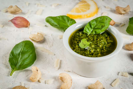 Italian and Mediterranean cuisine. Pesto sauce with ingredients on a white stone table: Parmesan cheese, cashew nuts, butter, lemon, basil.