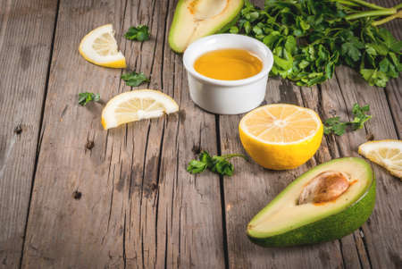 cooking oil: Ingredients of a healthy diet. Dressing for salad. Avocado, olive oil, lemon and parsley on a wooden rustic table. Copy space