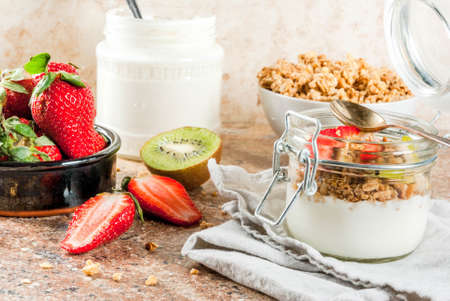Healthy breakfast. Diet. Overnight oatmeal in a can, muesli. Yogurt with homemade granola and organic fruits - kiwi, banana, strawberry. On tray on stone table.  Copy space Stock Photo
